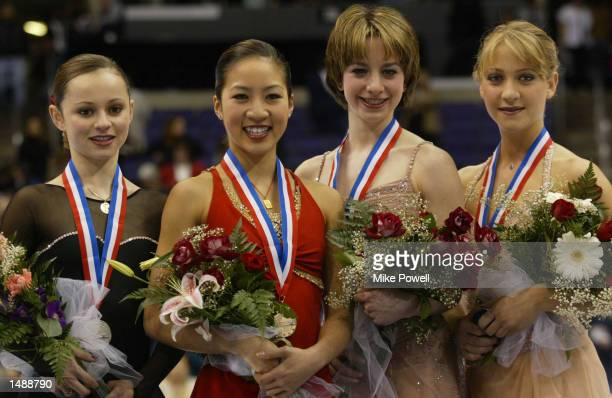Sasha Cohen, silver, Michelle Kwan, gold, Sarah Hughes, bronze and Angela Nikodinov, fourth all of the USA pose on the podium after receiving their...