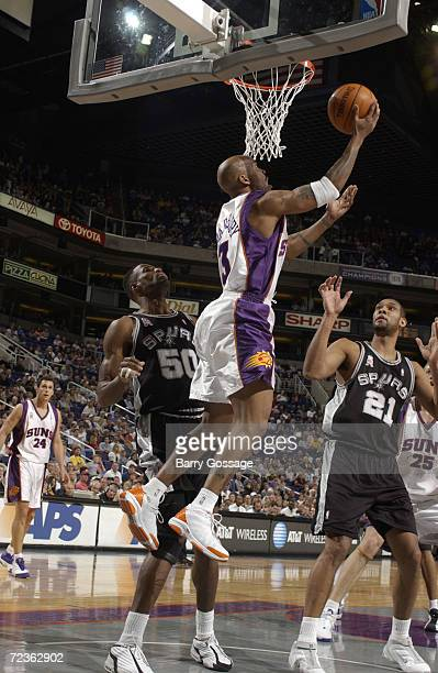 Stephon Marbury of the Phoenix Suns goes to the basket against David Robinson and Tim Duncan of the San Antonio Spurs during their game at America...