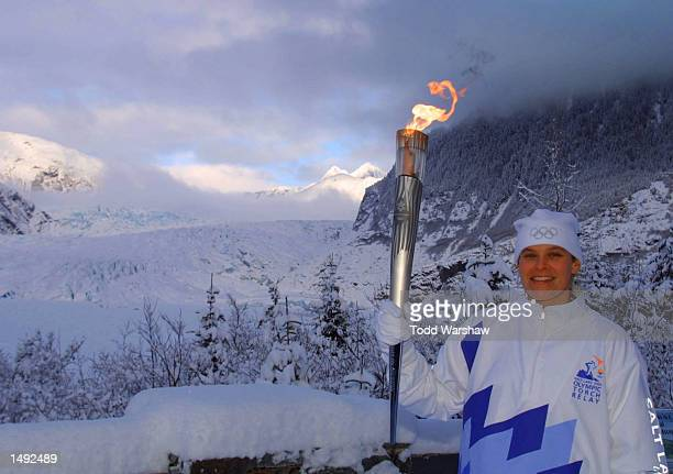 Torchbearer Hilary Lindh carries the Olympic Flame in front of the Mendenhall Glacier during the 2002 Salt Lake Olympic Torch Relay in Juneau Alaska...