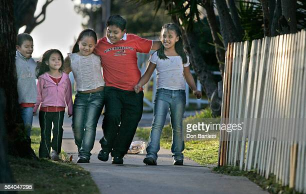 Jan 25 06 Costa Mesa CA Francisco Tadel 10 has a good time escorting his sisters and cousins along Shalimar St near their home Here on the west side...