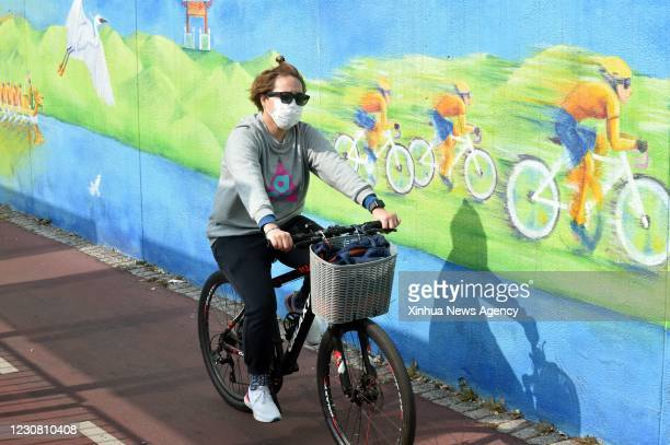 Jan. 26, 2021 -- A resident wearing a face mask rides a bike in south China's Hong Kong, Jan. 26, 2021. Hong Kong's Center for Health Protection CHP...