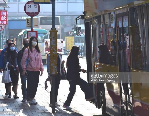Jan. 26, 2021 -- People wearing face masks get on a bus in south China's Hong Kong, Jan. 26, 2021. Hong Kong's Center for Health Protection CHP...
