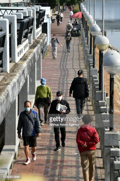 Jan. 26, 2021 -- Residents wearing face masks are seen in a street in south China's Hong Kong, Jan. 26, 2021. Hong Kong's Center for Health...