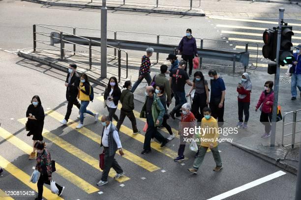 Jan. 26, 2021 -- Residents wearing face masks cross a street in south China's Hong Kong, Jan. 26, 2021. Hong Kong's Center for Health Protection CHP...