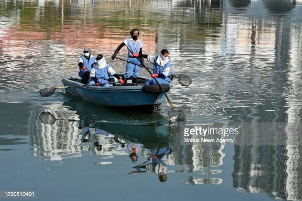 Jan. 26, 2021 -- Staff members clean the watercourse of Shing Mun river in south China's Hong Kong, Jan. 26, 2021. Hong Kong's Center for Health...