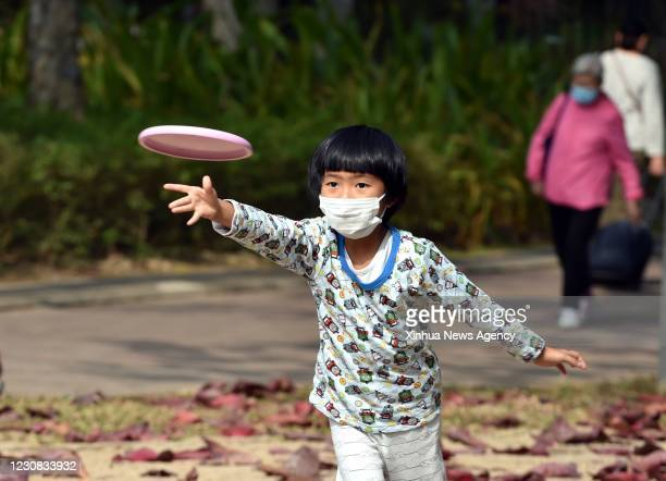 Jan. 27, 2021 -- A kid throws a frisbee in south China's Hong Kong, Jan. 27, 2021. Hong Kong's Center for Health Protection CHP reported 60...