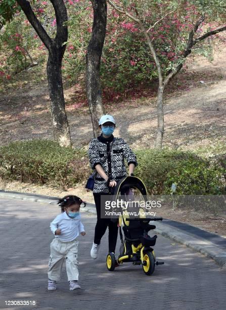 Jan. 27, 2021 -- Citizens take a walk at a park in south China's Hong Kong, Jan. 27, 2021. Hong Kong's Center for Health Protection CHP reported 60...