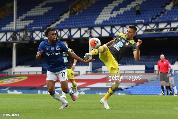 Jan Bednarek of Southampton is challenged by Alex Iwobi of Everton during the Premier League match between Everton FC and Southampton FC at Goodison...