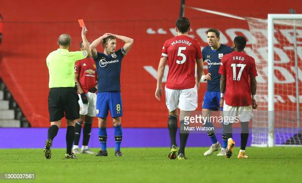 Jan Bednarek of Southampton is shown a red card by referee Mike Dean during the Premier League match between Manchester United and Southampton at Old...