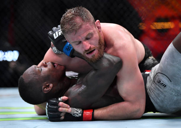Jan Blachowicz of Poland controls Israel Adesanya of Nigeria on the ground in their UFC light heavyweight championship fight during the UFC 259 event...