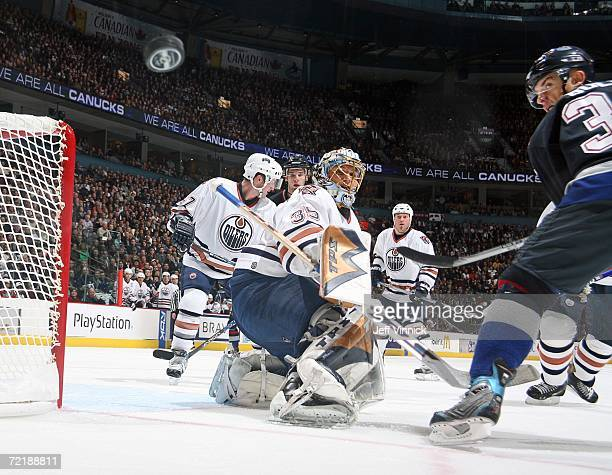 Jan Bulis of the Vancouver Canucks watches his shot miss the net as Dwayne Roloson of the Edmonton Oilers looks on during their NHL game at General...