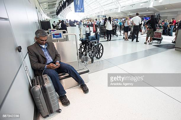 Jan Desouza checks his emails as he uses the baggage weigh station as a seat as he waits in line for updates from Delta airline employees regarding...