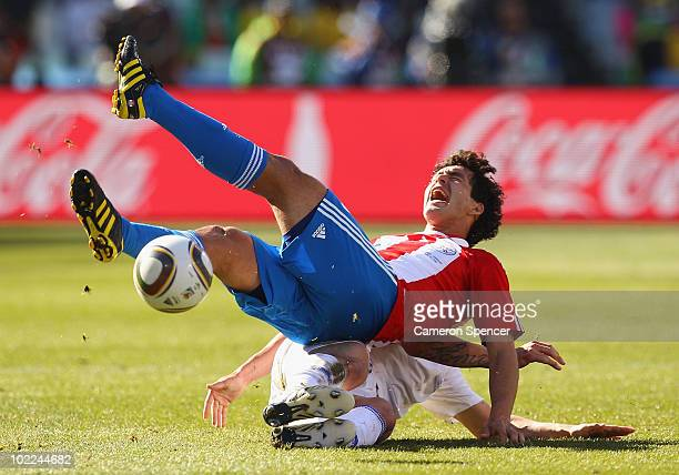 Jan Durica of Slovakia slides in a tackle on Cristian Riveros of Paraguay during the 2010 FIFA World Cup South Africa Group F match between Slovakia...