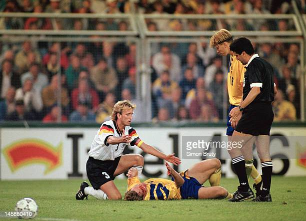 Jan Eriksson of Sweden goes down after a challenge from Andreas Brehme of Germany during the UEFA European Championships 1992 SemiFinal between...