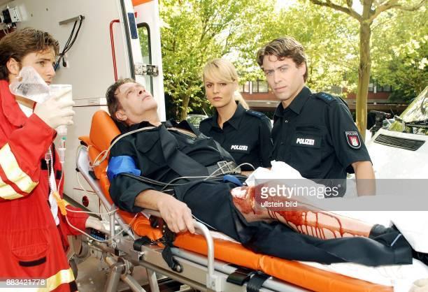 Jan Fedder Schauspieler D als Dirk Matthies vom Großstadtrevier mit Verletzung auf der Trage daneben Anja Nejarri als Katja Metz und Sebastian Hölz...