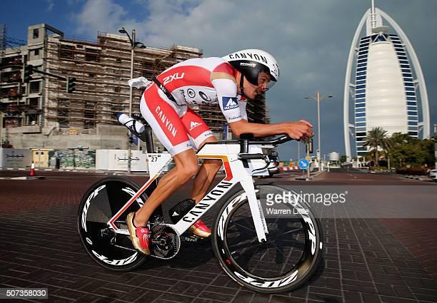 Jan Frodeno of Germany cycles past the Burj Al Arab en route to winning the Men's IRONMAN 703 Dubai on January 29 2016 in Dubai United Arab Emirates