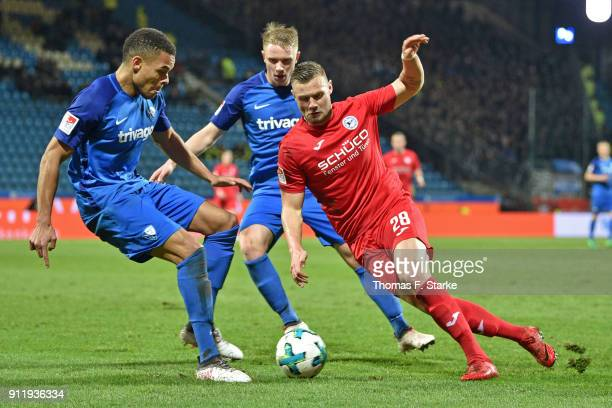 Jan Gyamerah and Philipp Ochs of Bochum tackle Florian Hartherz of Bielefeld during the Second Bundesliga match between VfL Bochum 1848 and DSC...
