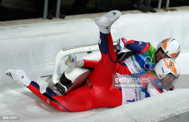 Jan Harnis and Branislav Regec of Slovakia wipe out after finishing the Luge Doubles final on day 6 of the Vancouver 2010 Winter Olympics at the...