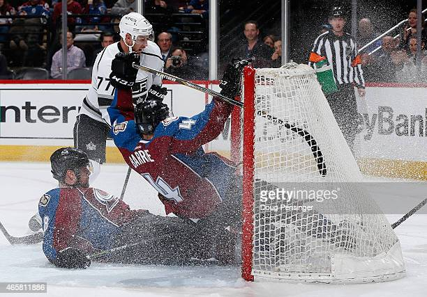 Jan Hejda and Tyson Barrie of the Colorado Avalanche crash into the goal as they defend an empty net against Jeff Carter of the Los Angeles Kings at...