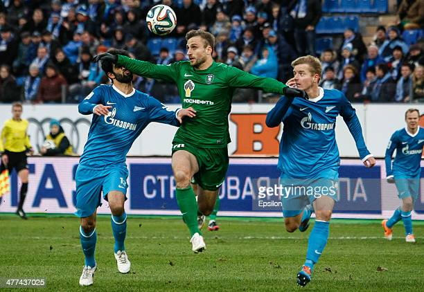 Jan Holenda of FC Tom Tomsk vies for the ball with Luis Neto of FC Zenit St Petersburg and Tomas Hubocan of FC Zenit St Petersburg during the Russian...