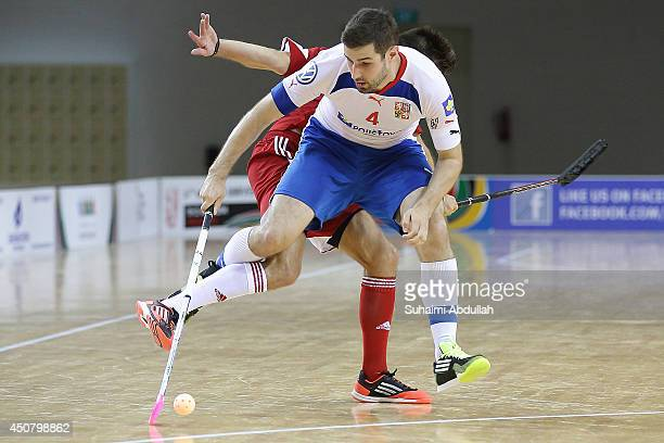 Jan Jelinek of Czech Republic vies for the ball with Bolliger Silvan of Switzerland during the World University Championship Floorball match between...