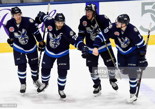 Jan Kostalek Patrice Cormier Brendan Lemieux and Buddy Robinson of the Manitoba Moose celebrate their 51 win over the Toronto Marlies on December 17...