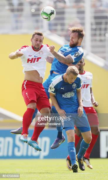 Jan Loehmannsroeben and Marius Groesch of Jena challenge Maik Kegel of Köln during the 3Liga match between FC Carl Zeiss Jena and SC Fortuna Köln at...