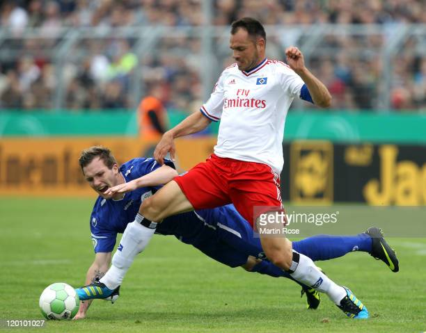 Jan Loehmannsroeben of Oldenburg and Heiko Westermann of Hamburg battle for the ball during the DFB Cup first round match between VfB Oldenburg and...