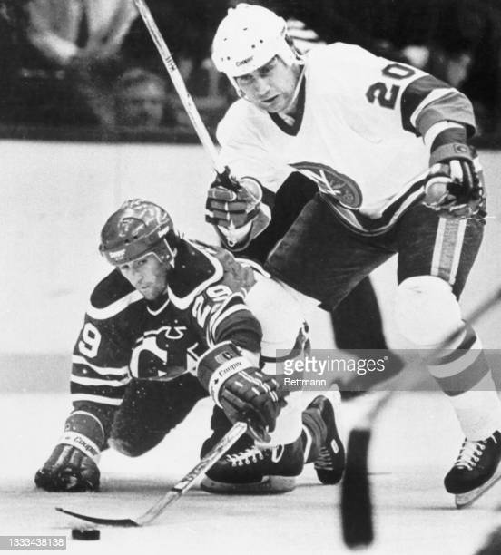 Jan Ludvig of the New Jersey Devils and Mats Hallin of the New York Islanders scramble for the loose puck on the ice.