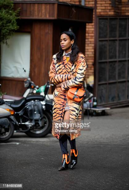 Jan Michael Quammie seen wearing orange coat with tiger print, bag, knee socks, ankle boots during day 1 of the Mercedes-Benz Tbilisi Fashion Week on...