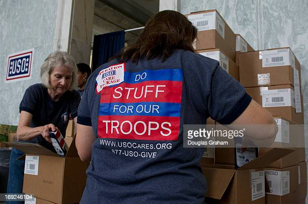 Jan Morgan and Patty Tarpey USO volunteers help organize goods to be packed and sent to the troops overseas in the Rayburn House Office Building...