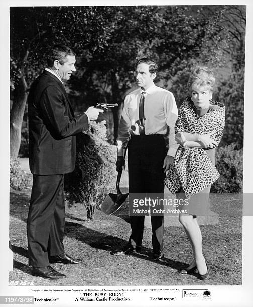 Jan Murray points gun at Sid Caesar while Anne Baxter freezes in a scene from the film 'The Busy Body' 1966