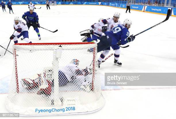 Jan Mursak of Slovenia falls to the ice after a play at the net against Lars Haugen of Norway in the first period during the Men's Play-offs...