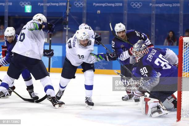 Jan Mursak of Slovenia scores the tying goal against Ryan Zapolski of the United States in the third period during the Men's Ice Hockey Preliminary...