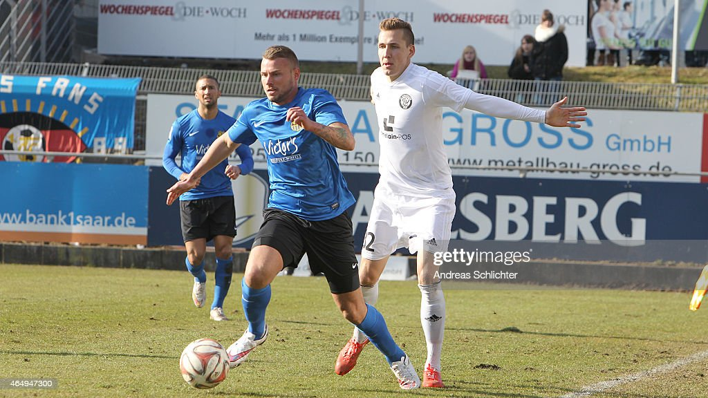 Jan Nagel of Elversberg with Dennis Wegner of Saarbruecken during the Regionalliga Suedwest match between SV Elversberg (white) and 1. FC Saarbruecken (blue) on February 28, 2015 in Neunkirchen, Germany.