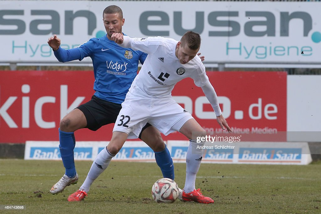 Jan Nagel of Elversberg with Mounir Chaftar of Saarbruecken during the Regionalliga Suedwest match between SV Elversberg (white) and 1. FC Saarbruecken (blue) on February 28, 2015 in Neunkirchen, Germany.