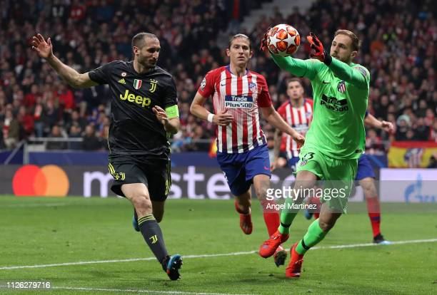 Jan Oblak of Atletico Madrid is challenged by Giorgio Chiellini of Juventus during the UEFA Champions League Round of 16 First Leg match between Club...