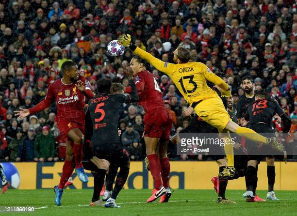 Jan Oblak of Atletico Madrid makes a save under pressure from Georginio Wijnaldum and Virgil van Dijk of Liverpool during the UEFA Champions League...