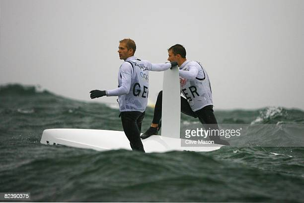 Jan Peter Peckolt and Hannes Peckolt of Germany capsize after competing in the 49er class race held at the Qingdao Olympic Sailing Center during day...