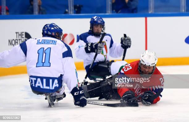 Jan Roger Klakegg of Norway battles for the puck with Nils Larch of Italy in the Ice Hockey Preliminary Round Group A game between Norway and Italy...
