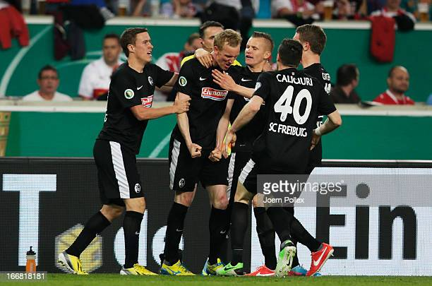 Jan Rosenthal of Freiburg celebrates with his team, mates after scoring his team's first goal during the DFB Cup Semi Final match between VfB...