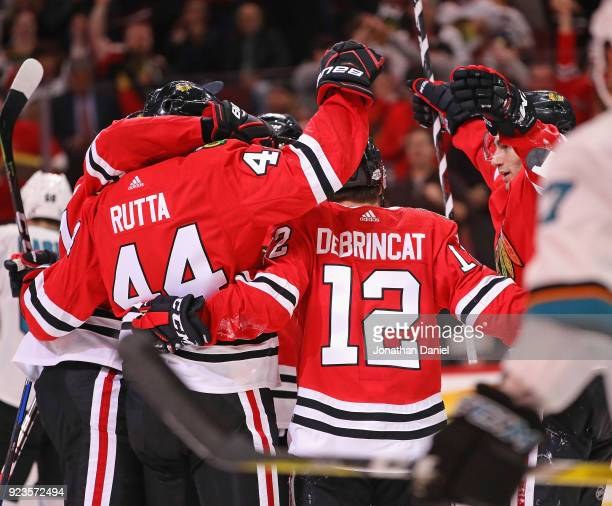 Jan Rutta Alex DeBrincat and Nick Schmaltz of the Chicago Blackhawks celebrate Ruttas' second period goal against the San Jose Sharks at the United...