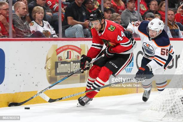 Jan Rutta of the Chicago Blackhawks and Anton Slepyshev of the Edmonton Oilers chase the puck in the third period at the United Center on October 19...