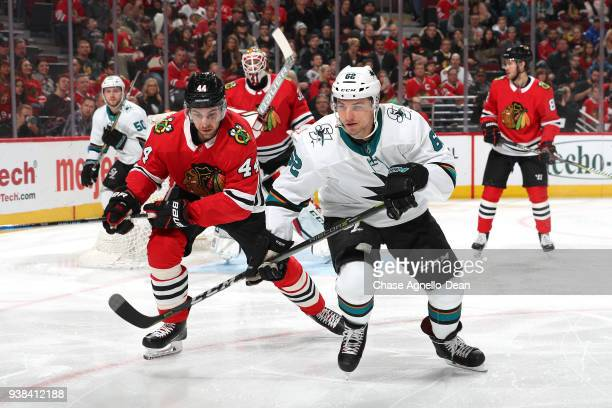 Jan Rutta of the Chicago Blackhawks and Kevin Labanc of the San Jose Sharks watch for the puck in the first period at the United Center on March 26...