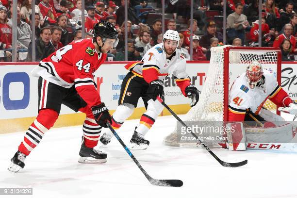 Jan Rutta of the Chicago Blackhawks and TJ Brodie of the Calgary Flames watch the puck next to goalie Mike Smith in the second period at the United...