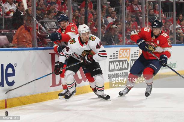 Jan Rutta of the Chicago Blackhawks battles for control of the puck with Jonathan Huberdeau and Aleksander Barkov of the Florida Panthers during...