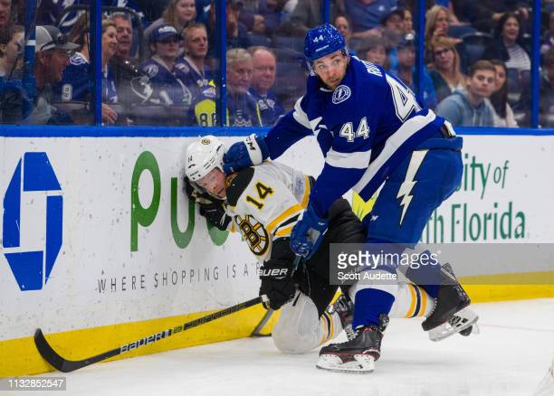 Jan Rutta of the Tampa Bay Lightning pushes Chris Wagner of the Boston Bruins into the boards during the second period at Amalie Arena on March 25...