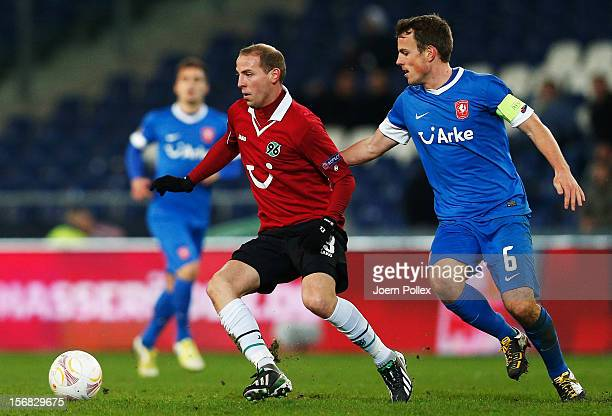 Jan Schlaudraff of Hannover and Wout Brama of Twente compete for the ball during the UEFA Europa League Group L match between Hannover 96 and FC...