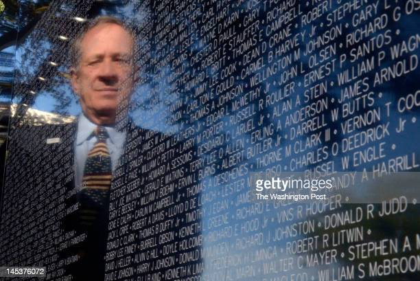 Jan Scruggs founder and president of the Vietnam Veterans Memorial Fund is reflected among the names of fallen soldiers on the traveling Vietnam...