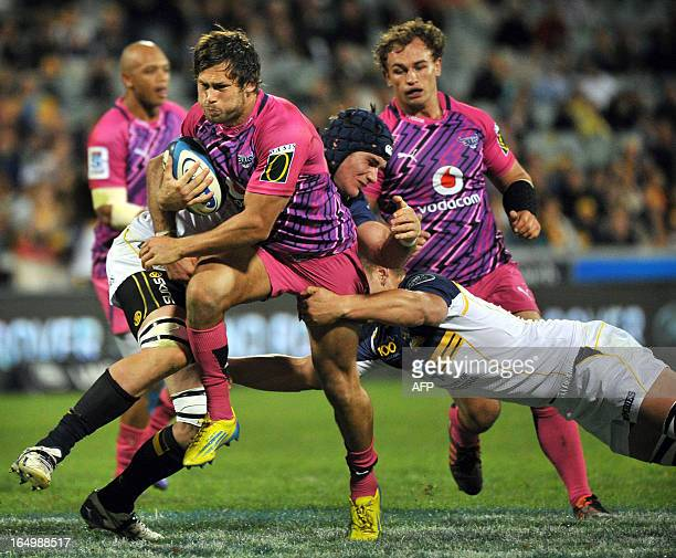 Jan Serfontein of the Bulls is tackled by Brumbies players during round 7 of the rugby Super 15 match in Canberra on March 30 2013 AFP PHOTO / Mark...